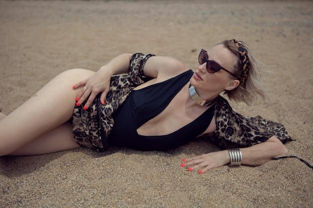 Mulher sexy em um maiô preto e óculos escuros está deitada na praia no verão