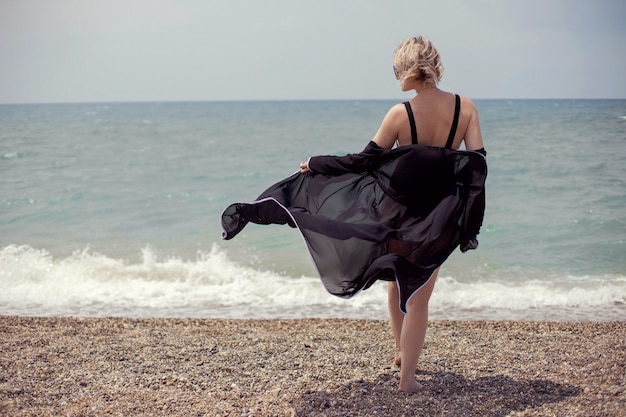 Mulher sexy em um maiô preto e óculos escuros fica em uma barraca na praia no verão