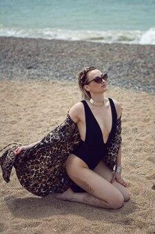 Mulher sexy em um maiô preto e óculos escuros sentada na praia no verão