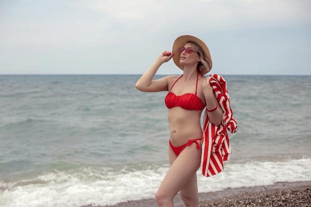 Mulher sexy em um maiô vermelho, uma jaqueta listrada, óculos escuros e um chapéu de palha fica na praia à beira-mar no verão