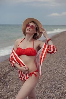 Mulher sexy em um maiô vermelho, uma jaqueta listrada, óculos escuros e um chapéu de palha fica na praia