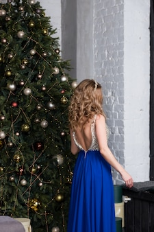 Mulher sexy em um vestido longo azul fica em uma sala de estar festiva sobre as luzes da árvore de natal. tema de ano novo e natal. humor de férias. modelo de menina moda com longos cabelos loiros em festivo bonito