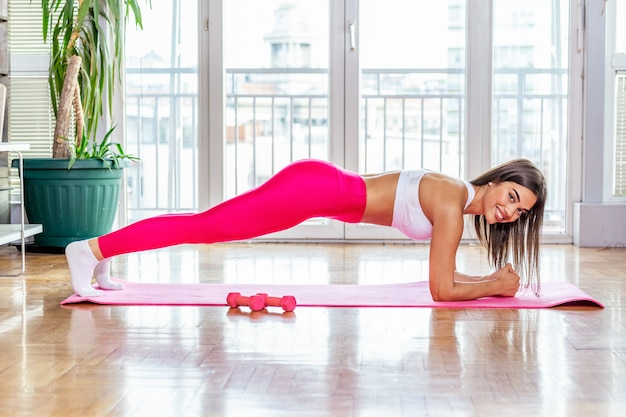 Mulher sexy fazendo prancha. jovem morena atraente com ajuste corpo malhando na aula de yoga. conceito de estilo de vida saudável