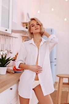 Mulher sexy. linda mulher sexy com corte bob em pé na cozinha usando calcinha e camiseta