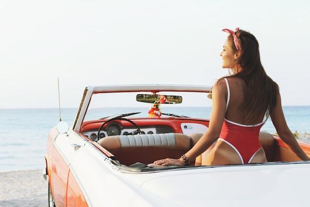 Mulher sexy maiô vermelho e carro conversível retrô
