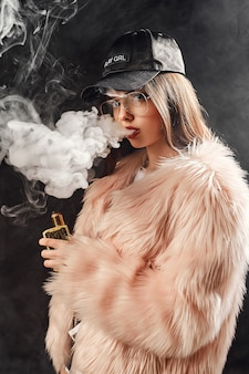 Mulher sexy na moda com casaco de pele rosa e boné fumando com cigarro eletrônico