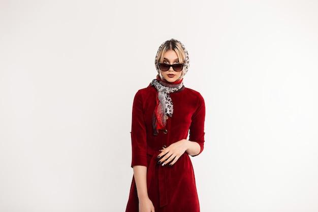 Mulher sexy na moda jovem em óculos de sol em xale estampa de leopardo retrô vintage em borgonha lindo vestido posando perto de uma parede branca dentro de casa.