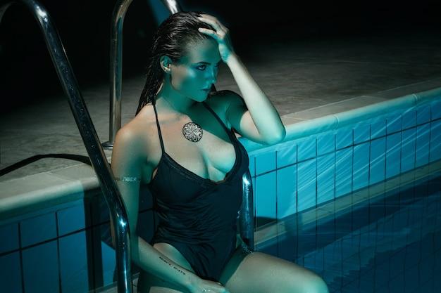 Mulher sexy na piscina à noite