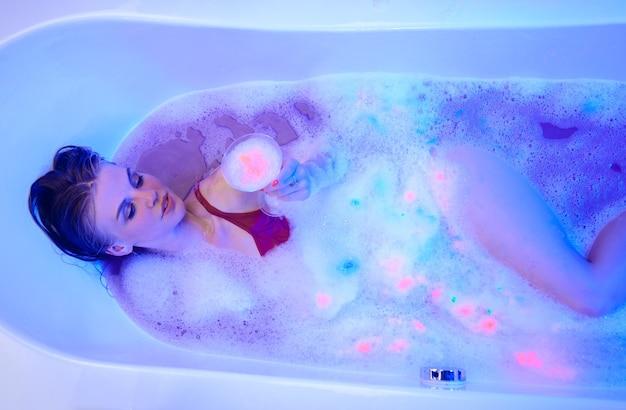 Mulher sexy no banho com luzes de néon néon spa banho tempo lavagem corporal espuma cuidados com o cabelo na bolha de shampoo para a cabeça