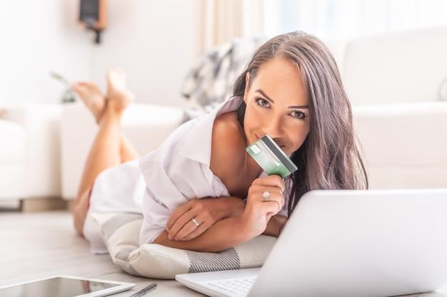 Mulher sexy olhando para a câmera cobrindo a boca com um cartão de pagamento, deitada no chão vestida apenas com sua camisa branca com um caderno aberto e um tablet ao lado dela.