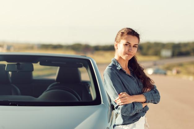 Mulher sexy, posando ao lado do carro cabrio