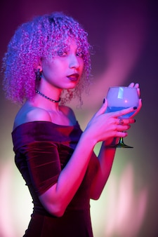Mulher sexy segurando uma bebida noturna em uma festa de halloween