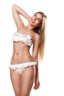 Mulher sexy slim bronzeada em maiô branco em estúdio isolado com tecido