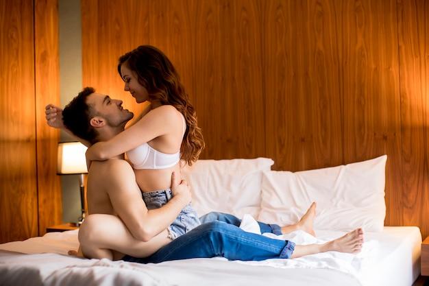 Mulher sexy sutiã sentar no bonitão e abraçá-lo com as pernas em uma cama
