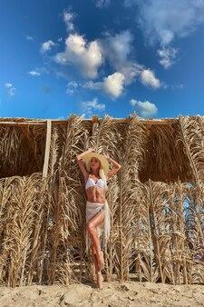 Mulher sexy usando biquíni em pé numa espreguiçadeira sob o dossel de palha na piscina do resort