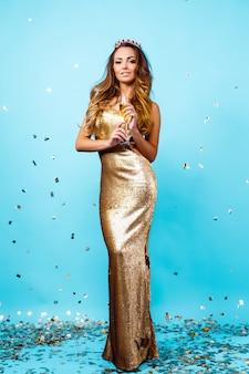 Mulher sexy vestido dourado e coroa com champanhe