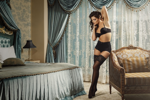 Mulher sexy vestindo uma lingerie bonita está posando no quarto