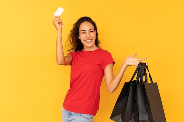 Mulher shopaholic alegre carregando sacolas de papel preto sobre fundo amarelo.