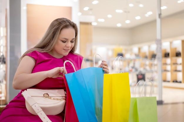 Mulher shopaholic sorridente plus size posando relaxando durante a negra sexta-feira com desconto no shopping center