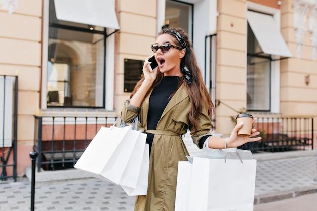 Mulher shopaholic surpresa descobriu grandes descontos na loja durante uma conversa com um amigo
