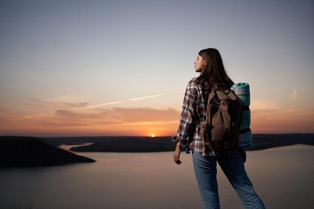 Mulher simpática com mochila apreciando o pôr do sol da colina