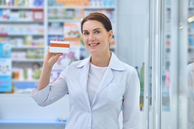 Mulher simpática de jaleco branco mostrando remédio