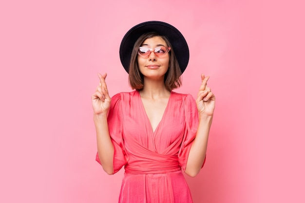 Mulher simpática e alegre deseja fazer o seu melhor para manter os dedos cruzados, tem o melhor, usando vestido isolado na parede rosa. pessoas, o conceito de linguagem corporal. copyspace.