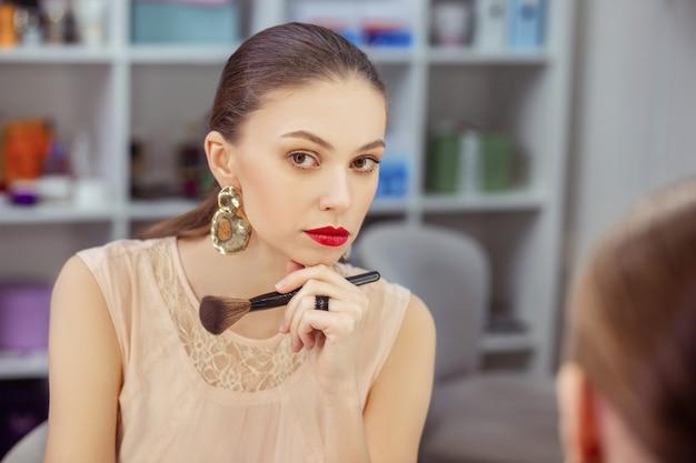 Mulher simpática e atenciosa sentada em frente ao espelho enquanto pensa em seu visual