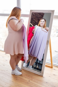 Mulher simpática e bonita em frente ao espelho enquanto escolhe entre os vestidos
