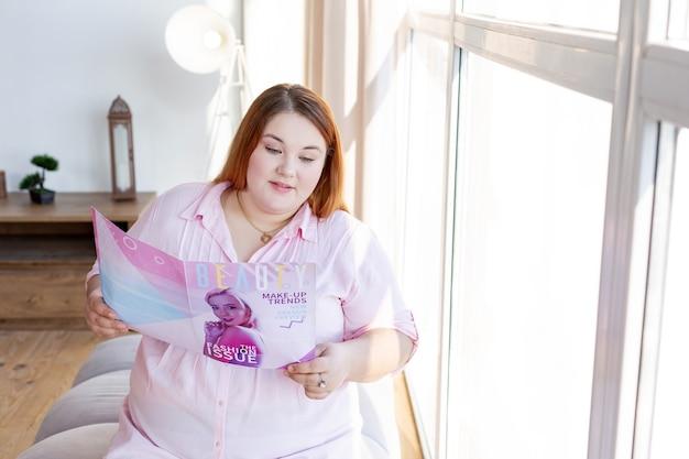Mulher simpática e bonita lendo uma revista enquanto segue as tendências modernas