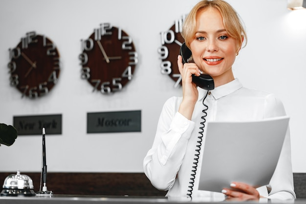 Mulher simpática e bonita recepcionista de hotel falando ao telefone de perto