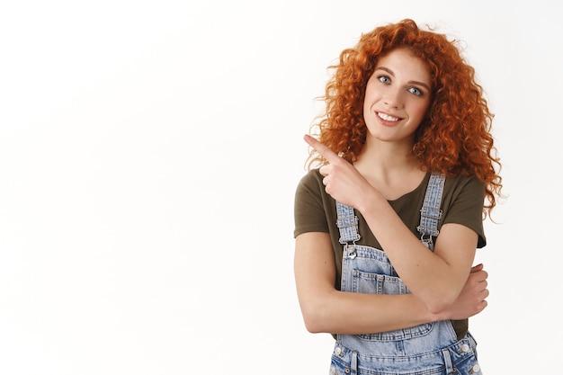 Mulher simpática e elegante ruiva caucasiana de cabelos cacheados convidar colegas de trabalho depois do trabalho, apontando o dedo para o espaço da cópia em branco, sorrindo despreocupada, mostrando uma proposta incrível, parede branca de pé
