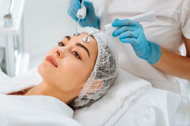 Mulher simpática e positiva deitada na cama médica durante um procedimento de terapia com microcorrentes