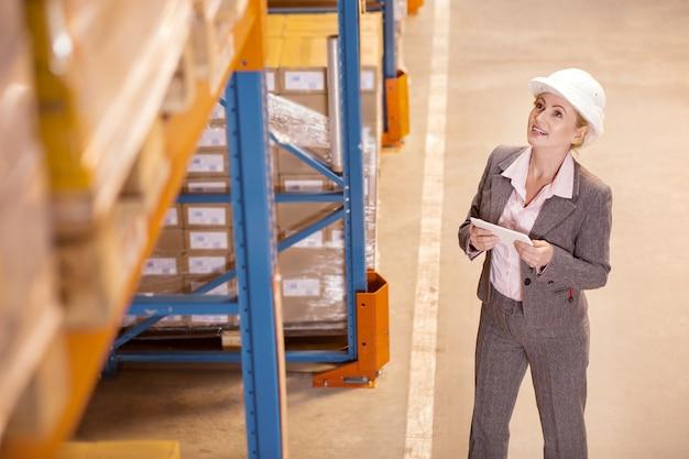 Mulher simpática e positiva olhando para o depósito enquanto trabalha como gerente de entrega no depósito