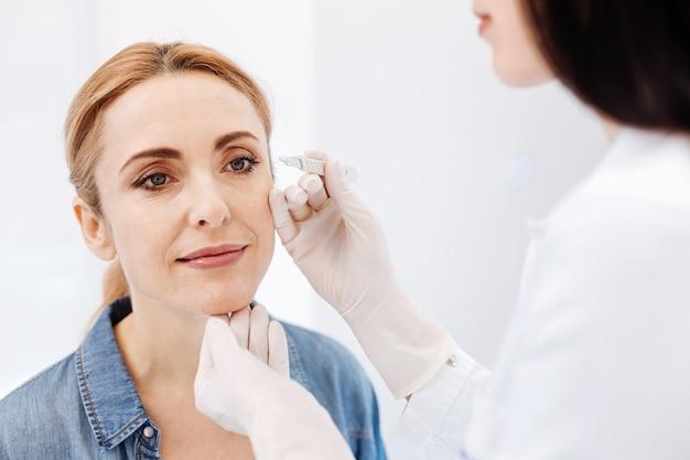 Mulher simpática e positiva sentada em frente ao cosmetologista sorrindo enquanto arranca as sobrancelhas