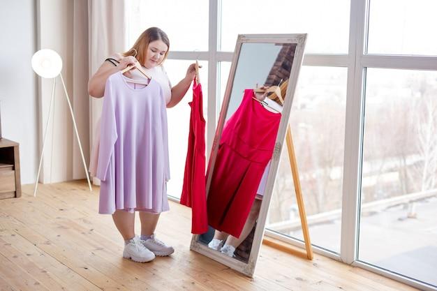 Mulher simpática e séria em frente ao espelho enquanto decide qual vestido usar