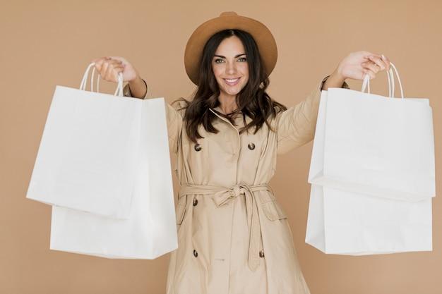 Mulher simpática no casaco com redes de compras em ambas as mãos