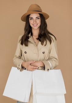 Mulher simpática no casaco e chapéu com redes de compras em ambas as mãos
