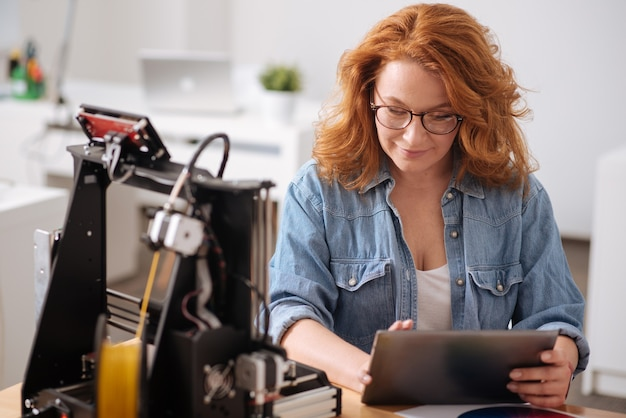 Mulher simpática, positiva e bonita segurando um tablet e olhando para a tela enquanto trabalha com tecnologia moderna