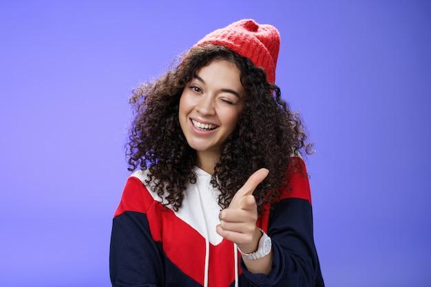 Mulher simpática, sociável e elegante, com cabelo encaracolado em um gorro vermelho piscando alegremente e apontando com a pistola de dedo para a câmera como companheiro de saudação sendo legal e confiante sobre a parede azul.