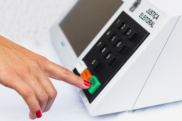 Mulher simula voto na urna eletrônica usada nas eleições do brasil