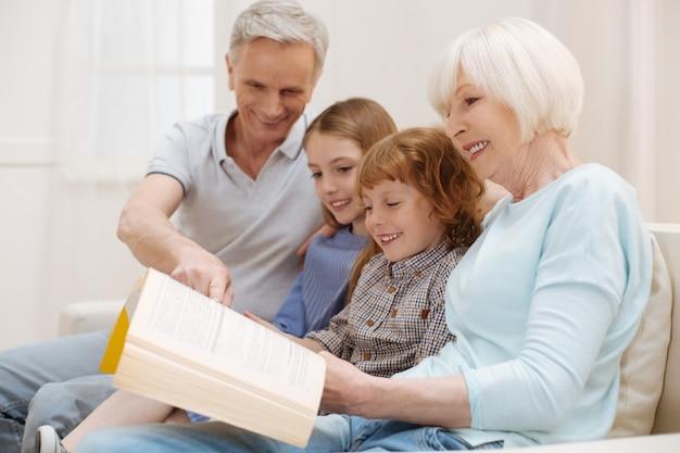Mulher sincera, criativa e incrível compartilhando seu livro favorito com crianças que a visitam e o avô no fim de semana