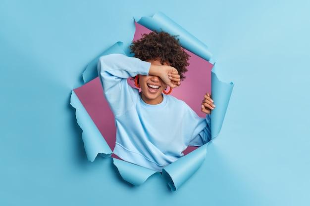 Mulher sincera de cabelo encaracolado cobre os olhos com risos no braço, positivamente, esconde os sorrisos do rosto e usa poses casuais de macacão através da parede de papel azul