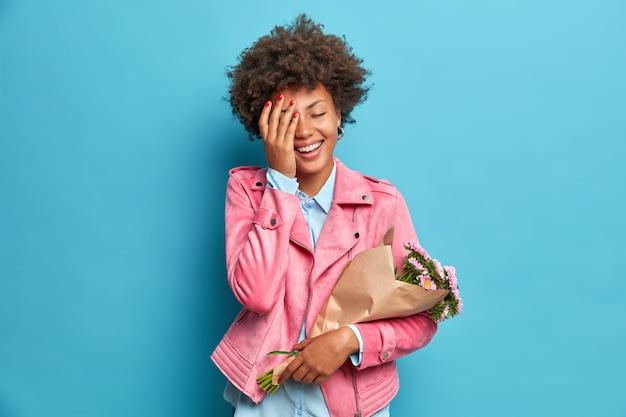Mulher sincera e positiva, vestida com roupas da moda, fica muito feliz em receber buquê de flores da pessoa amada fazendo rosto de palma isolada sobre parede azul
