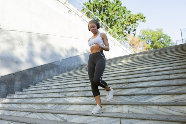 Mulher slim fit em roupas esportivas sobe as escadas ao ar livre. conceito de estilo de vida saudável