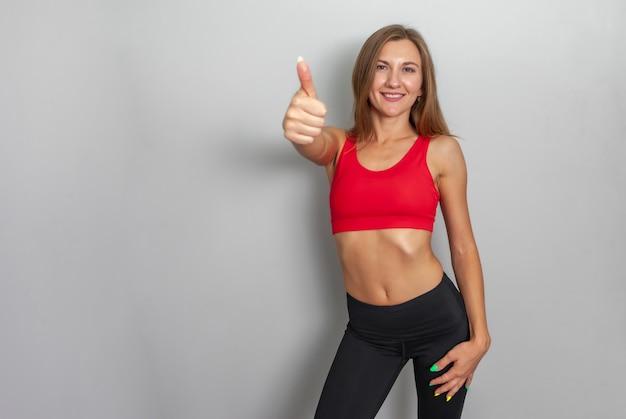 Mulher slim fit em sportswear aparecendo o polegar em fundo cinza