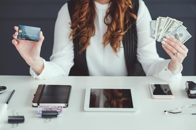 Mulher smm de sucesso. dinheiro fazendo negócios. feminina no local de trabalho, segurando notas de dólar de cartão de crédito.