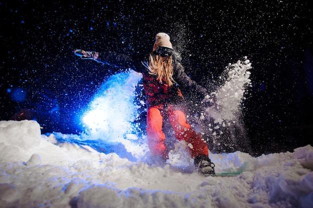Mulher snowboarder vestida com uma roupa esportiva vermelha andando na encosta da montanha à noite sob a luz azul