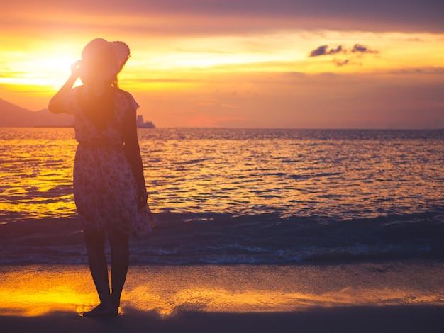 Mulher só e deprimida da silhueta que está na frente do mar.