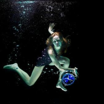 Mulher sob a água com um relógio